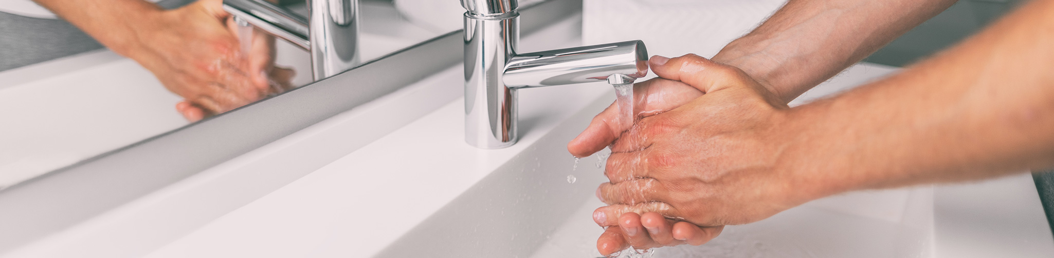 Person washing their hands over a sink.
