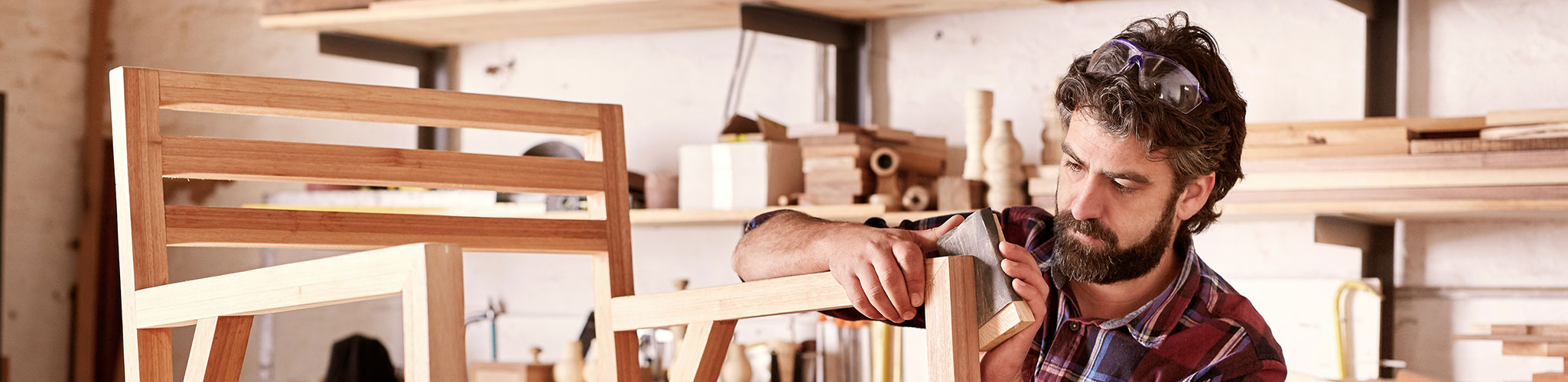 Bearded man building a chair in a workshop