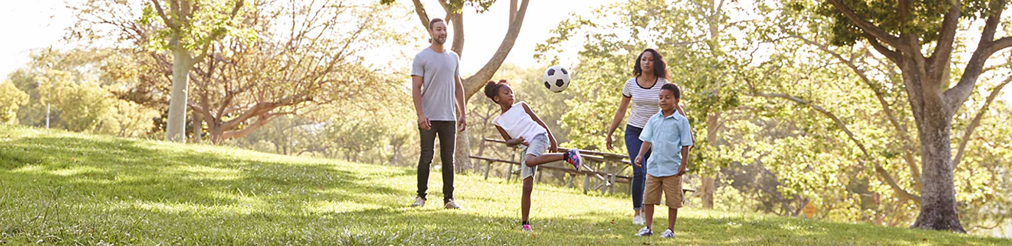 Young family playing soccer in a park.