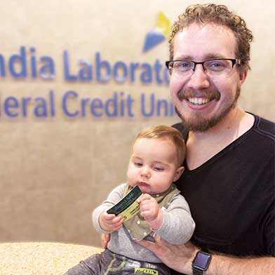 Ryan and Lincoln McCoy in front of Sandia Laboratory Federal Credit Union Logo