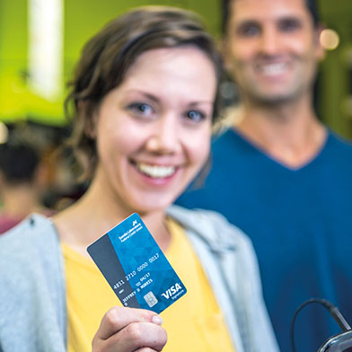Young woman smiling and holding an SLFCU Visa credit card